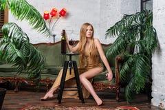 Trinkender Wein der Frau Schöne junge Blondine im langen goldenen Abendkleid mit Glas Rotwein im Luxusdachboden Stockfotografie