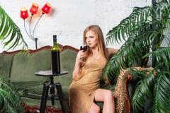 Trinkender Wein der Frau Schöne junge Blondine im langen goldenen Abendkleid mit Glas Rotwein im Luxusdachboden Lizenzfreie Stockfotos