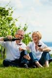 Trinkender Wein der glücklichen Paare in See am Sommer Lizenzfreie Stockbilder