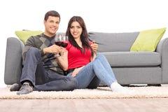 Trinkender Wein der jungen Paare gesetzt durch ein Sofa Lizenzfreies Stockfoto