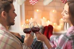 Trinkender Wein der Paare vor Kamin zu Hause Lizenzfreie Stockfotos