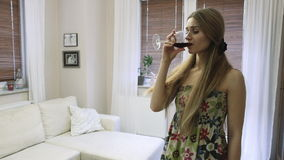 Trinkender Wein der traurigen hübschen Frau in einem Wohnzimmer
