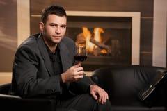 Trinkender Wein des Geschäftsmannes zu Hause stockfotos
