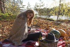 Trinkender Wein des Mädchens im Herbstwald Stockfoto