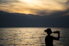 Trinkender Wein des Mädchens am Strand während des Sonnenuntergangs stockfotos
