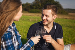 Trinkender Wein des Mannes und der Frau an einem Picknick Lizenzfreie Stockbilder