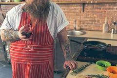 Trinkender Wein des starken Kerls beim Kochen lizenzfreies stockbild