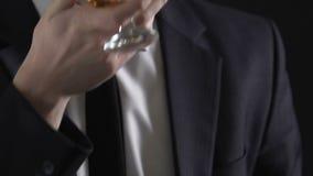 Trinkender Whisky des erfolgreichen Geschäftsmannes und Halten von Dollarscheinen, reiche Person stock footage