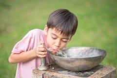 Trinkendes öffentliches Wasser des kleinen Jungen Stockbild