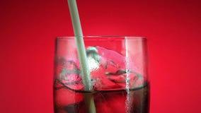 Trinkendes alkoholfreies Getränk im Glas mit Eiswürfel auf rotem Hintergrund Kolabaum oder Erfrischung stock video footage