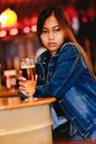 Trinkendes Bier der jungen Schönheit in einer Bar Stockfotos