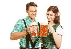 Trinkendes Bier der Paare im Bayern Stockbild