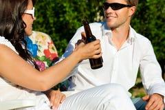 Trinkendes Bier der Paare am Sommer Lizenzfreie Stockfotos