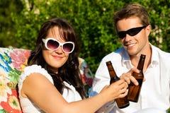 Trinkendes Bier der Paare am Sommer Stockfotos