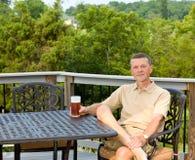 Trinkendes Bier des älteren Mannes im Garten Stockfotos