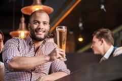 Trinkendes Bier des überzeugten Mannes an der Bar Mann hält Glas Bier Lizenzfreie Stockbilder