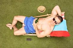 Trinkendes Bier des entspannten Kerls in seinem Hinterhof Stockfotos