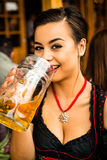 Trinkendes Bier des Mädchens bei Oktoberfest stockfotografie