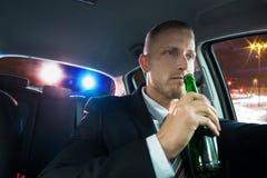 Trinkendes Bier des Mannes vorbei gezogen von der Polizei Stockbilder