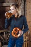 Trinkendes Bier und Essen einer Brezel Stockfotografie