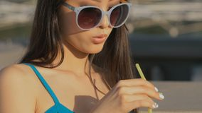Trinkendes Cocktail der jungen asiatischen Modefrau in einer Strandbar stock video footage