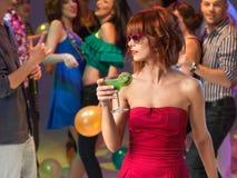 Trinkendes Cocktail der reizvollen Frau im Nachtclub Stockfotografie