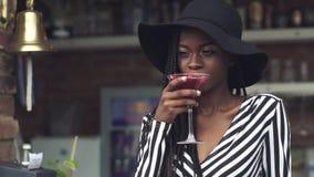 Trinkendes Cocktail herrlicher Afroamerikanergeschäfts-Dame an der Bar mit fantastischem Innenraum stock footage