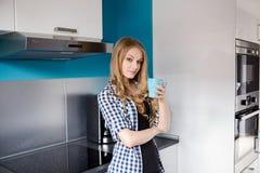 Trinkendes coffe oder Tee der blauäugigen blonden Frau von der Schale Stockfotos