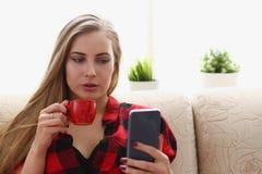 Trinkendes coffe und Blick der Frau auf Laptop Stockfotografie