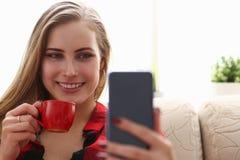 Trinkendes coffe und Blick der Frau auf Laptop Stockbilder