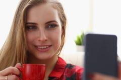 Trinkendes coffe und Blick der Frau auf Laptop Lizenzfreies Stockfoto