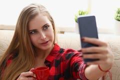 Trinkendes coffe und Blick der Frau auf Laptop Lizenzfreie Stockbilder