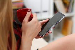 Trinkendes coffe und Blick der Frau auf Laptop Stockbild