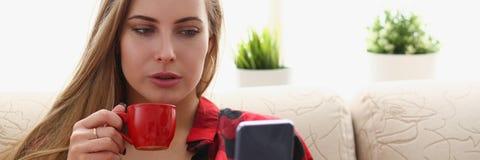 Trinkendes coffe und Blick der Frau auf Laptop Lizenzfreie Stockfotografie