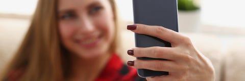 Trinkendes coffe und Blick der Frau auf Laptop Lizenzfreie Stockfotos