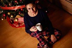 Trinkendes Getränk des Mädchens vor Weihnachtsbaum lizenzfreie stockfotos