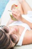 Trinkendes Kokosnusscocktail der jungen hübschen Frau Stockbild