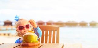 Trinkendes Kokosnusscocktail des kleinen Mädchens auf Strand Lizenzfreie Stockfotos
