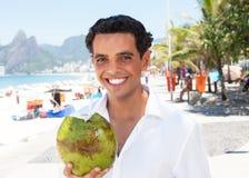 Trinkendes Kokosnusswasser des glücklichen lateinischen Kerls am Strand Lizenzfreie Stockfotos