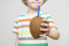 Trinkendes Kokosnusswasser des Kleinkindes Kleinkind, das eine Kokosnuss isst Das Kind trinkt Kokosnusssaft von einer ganzen Koko stockfotos