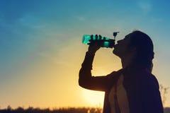 Trinkendes Tafelwasser der jungen Frau bei Sonnenuntergang Stockbilder