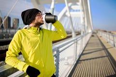 Trinkendes wasser- während der Übung draußen wieder hydratisieren des jungen Athletenmannes lizenzfreie stockbilder