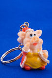 Trinket in the form of pig on blue. Velvet Royalty Free Stock Photography
