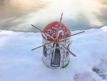 Trinket wind mill on the snow with frozen background. Wind mill on the snow with frozen background. Forzen swimming pool, frozen lake Royalty Free Stock Images