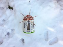 Trinket wind mill. In the snow near the feetprint Stock Image