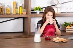 Trinkmilch der Frau im Wohnzimmer lizenzfreie stockfotos