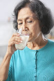 Trinkmilch der älteren Frau Stockbild