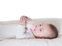 Trinkmilch des Babys von der Flasche lokalisiert Lizenzfreies Stockbild