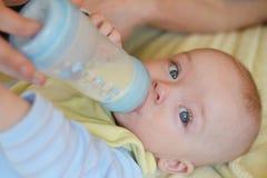 Trinkmilch des Babys von einer Flasche Stockbild