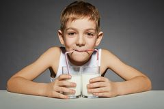 Trinkmilch des Jungen von zwei Gläsern Stockfotos